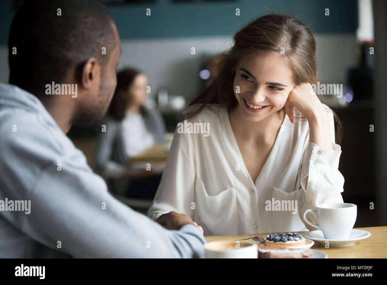 Happy young couple interracial flirter parler holding hands in Photo Stock