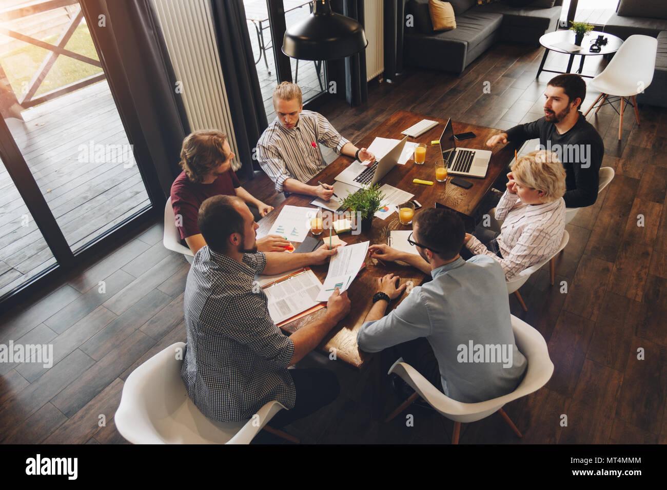 Employés d'entreprise créative travaillent sur de nouvelles discussions sur le démarrage et l'idée de développement des affaires. Les collègues s'asseoir autour de la table en bois et les travaux sur la Banque D'Images