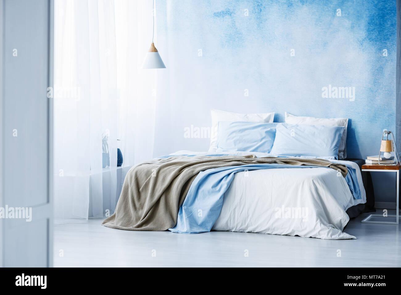 Jaune et bleu sur blanc literie lit dans chambre à coucher avec un ...