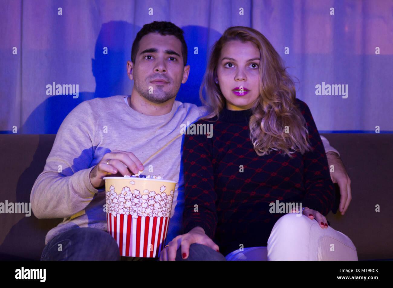 Jeune couple regardant thriller film dans une pièce sombre avec des pop-corn sur canapé attention entièrement Photo Stock