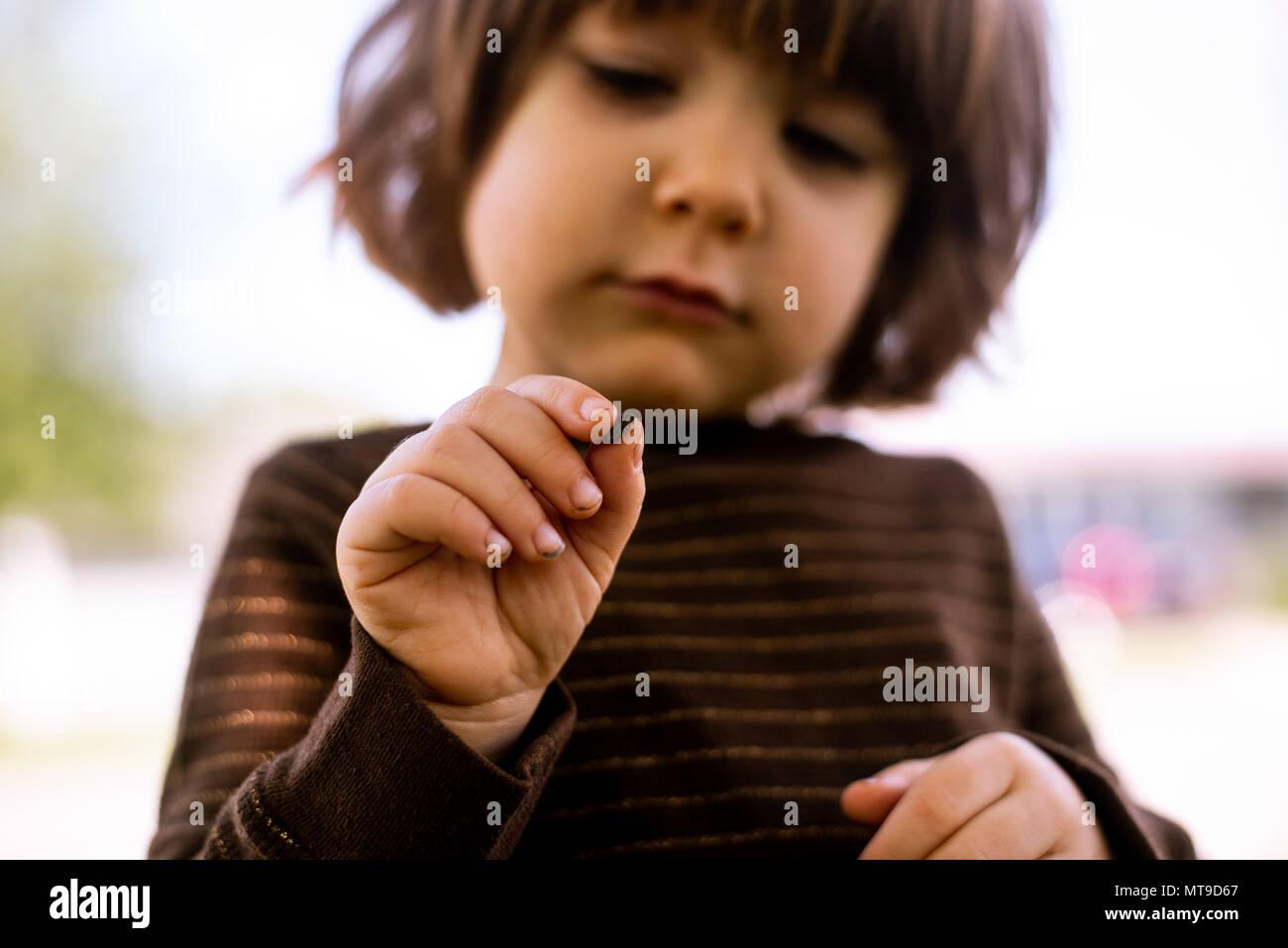 Un bébé fille tenant un bug dans ses mains. Photo Stock
