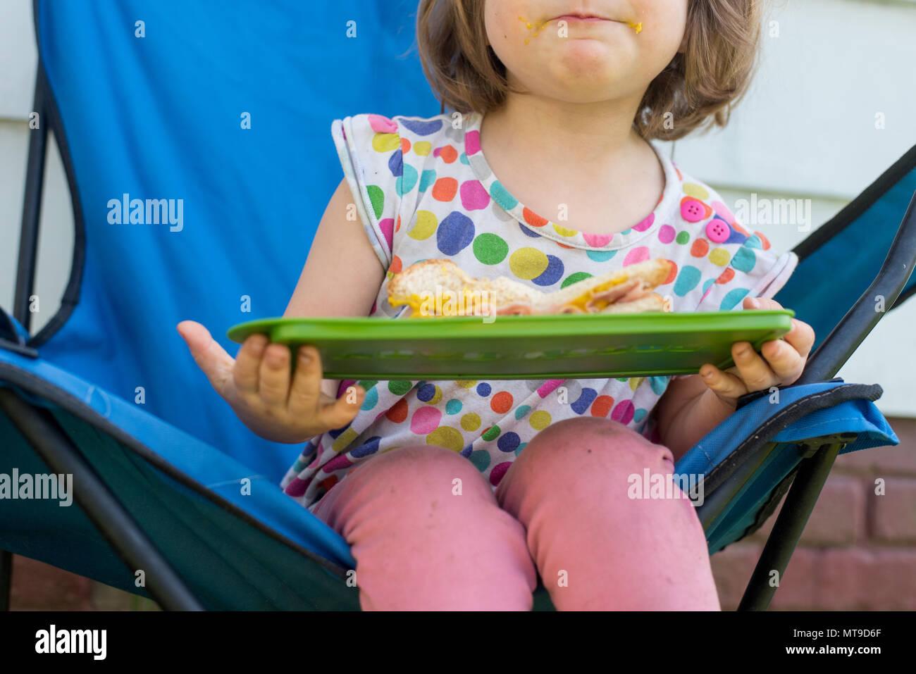 Un bébé fille tenant un sandwich au jambon à l'extérieur Photo Stock