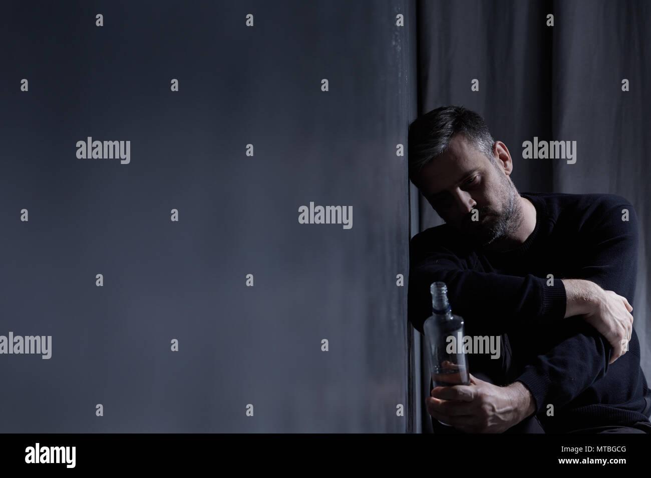 Man holding bouteille d'alcool dans l'intérieur sombre Photo Stock