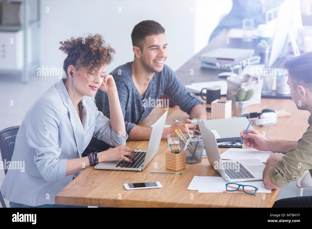 Les collègues ayant une discussion joyeuse dans leur bureau lors d'une pause Photo Stock