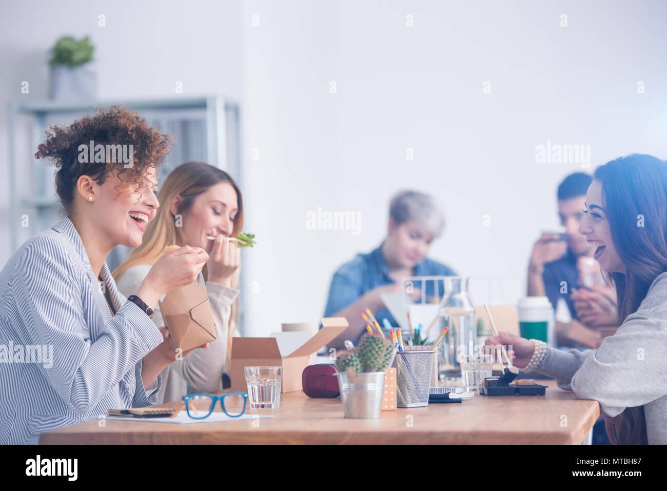 Les employés de race blanche de manger le déjeuner avec leur collègue mulâtre Photo Stock