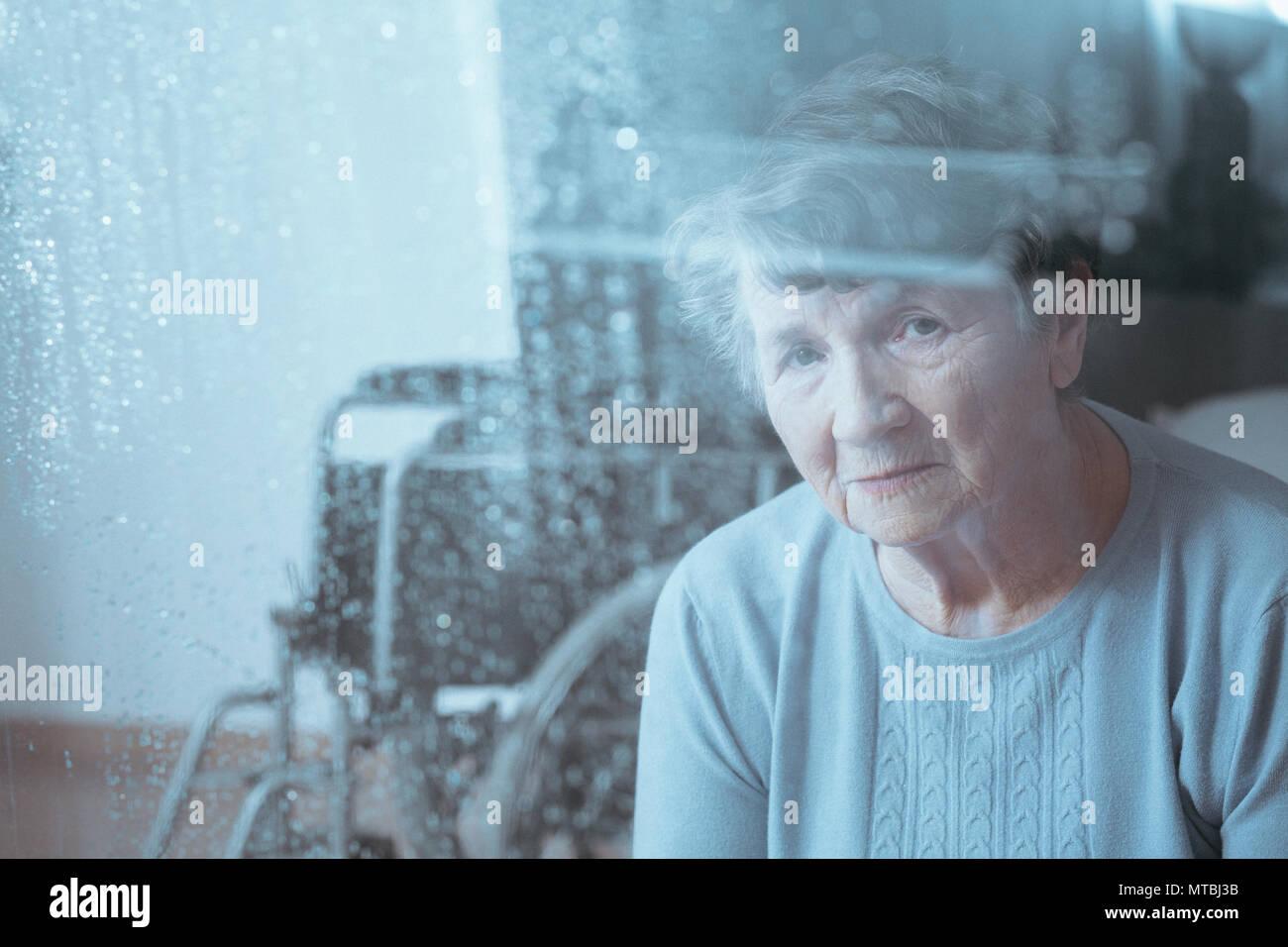 Triste, senior femme handicapée, en fauteuil roulant en arrière-plan Photo Stock