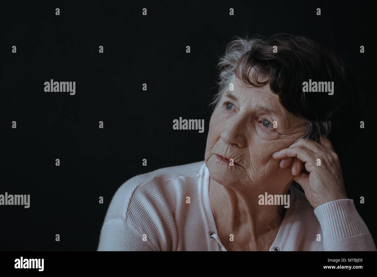 Portrait of senior woman, inquiets, fond noir Photo Stock