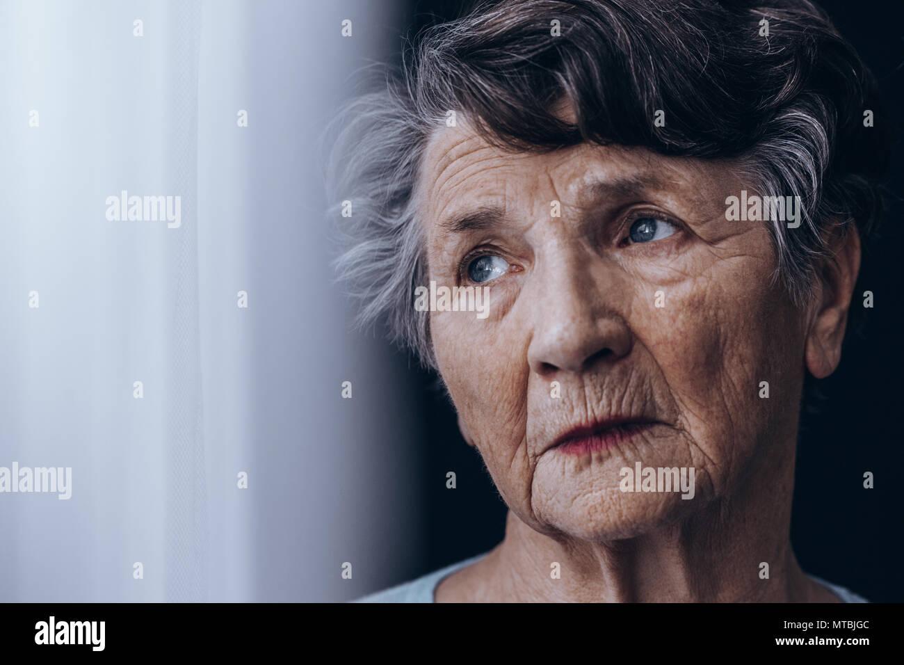 Portrait de désespoir, vieille femme debout à côté de fenêtre Photo Stock