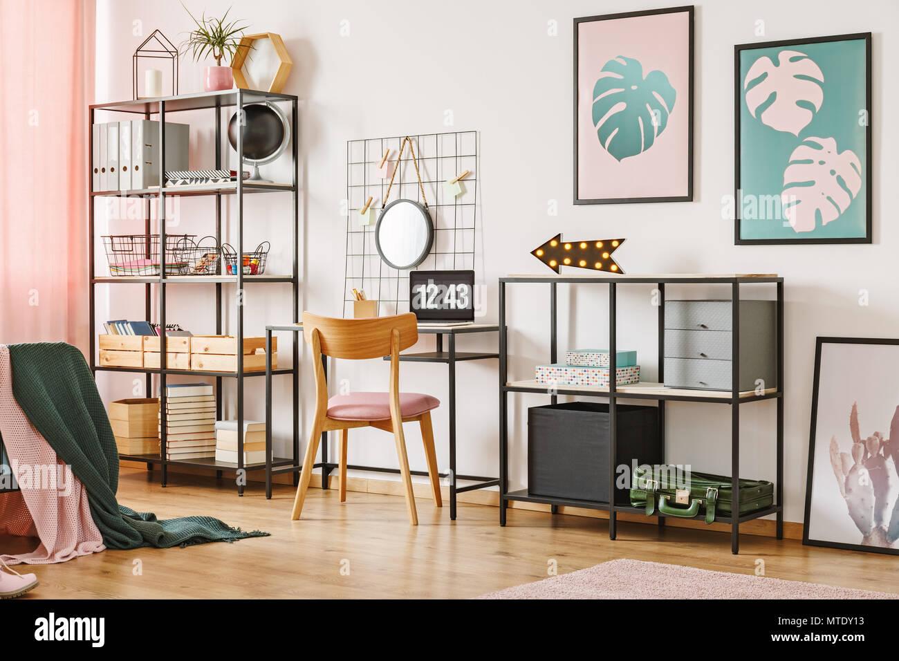 Chaise en bois un bureau et étagères noires avec des cases dans