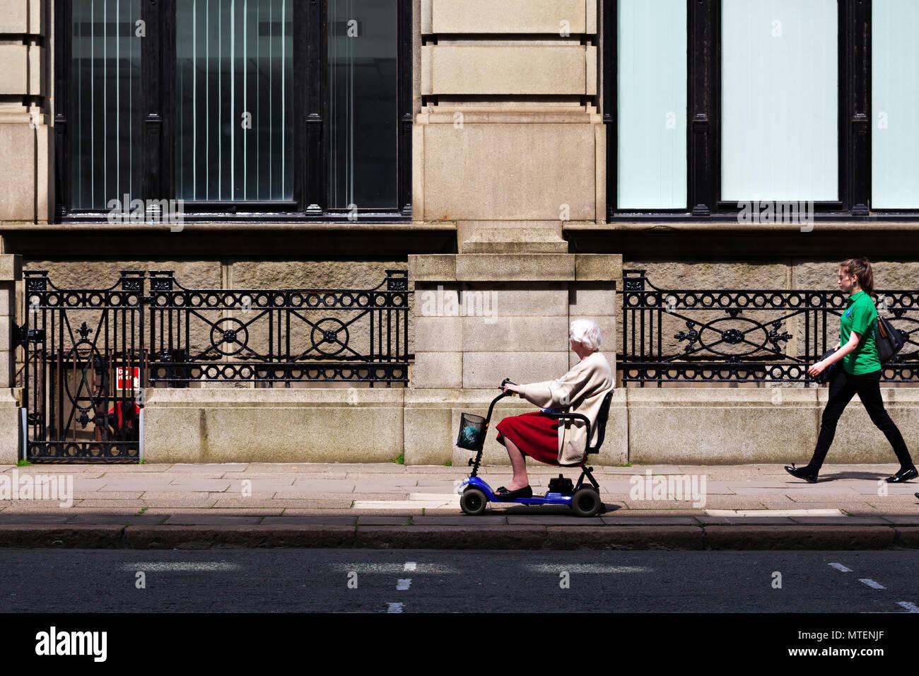 Une vieille femme sur un scooter de mobilité alors qu'une jeune femme passe devant elle. Photo Stock