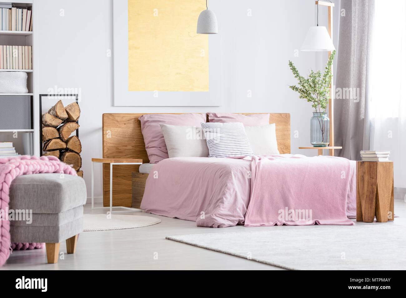 Grand lit en bois avec literie rose dans de confortables ...