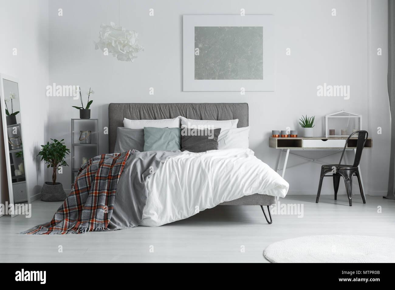 Checkered couverture jetée sur le lit dans une chambre avec bureau