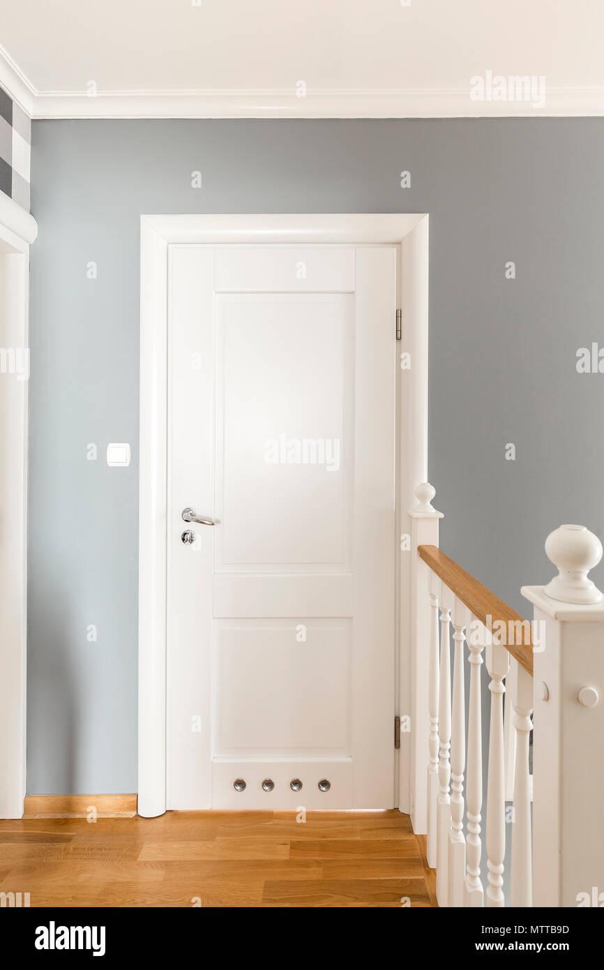 Couloir gris avec portes blanches et balustrade en bois simple ...