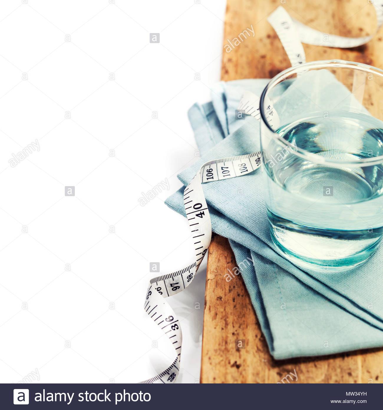 Verre d'eau et ruban à mesurer Photo Stock