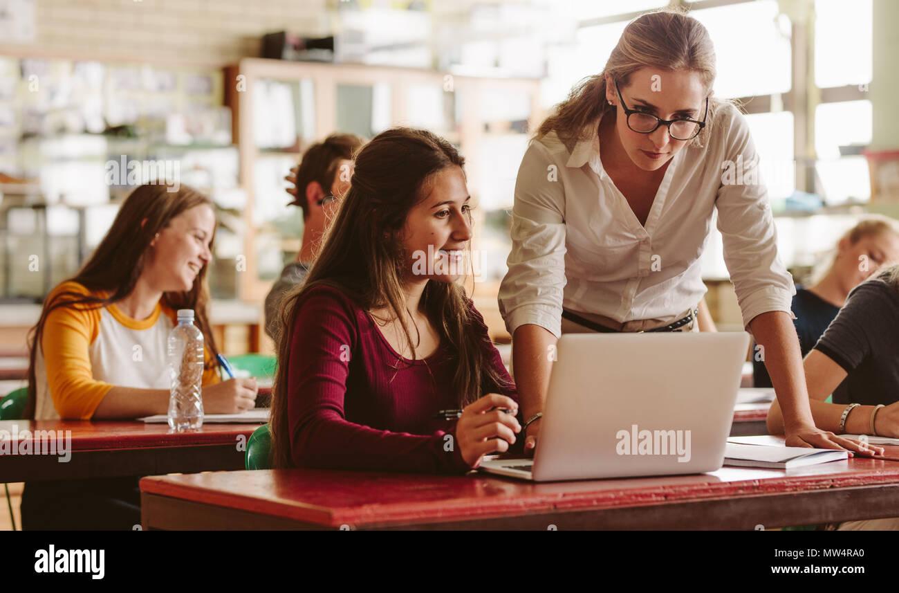 Portrait de jeune enseignant aider un étudiant en classe. Étudiant de l'Université d'être aidé par des femmes au cours de maître de classe. Photo Stock