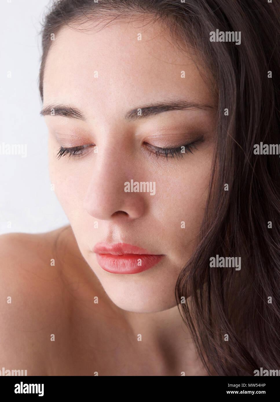 Jeune femme italienne avec les cheveux bruns et des lèvres rouges et plein les yeux baissés Photo Stock