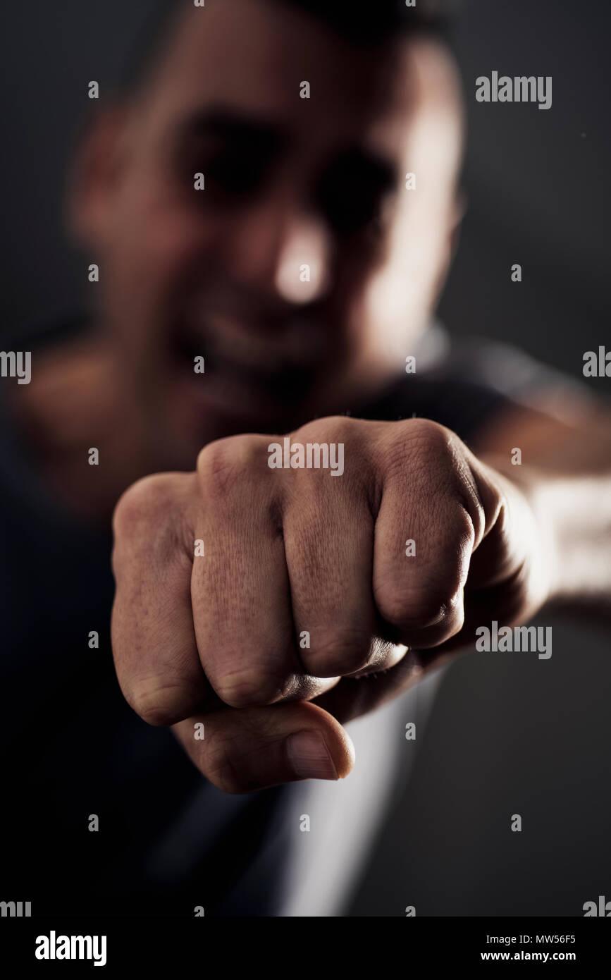 Closeup of a young caucasian man throwing a punch à l'observateur, avec un effet dramatique Photo Stock
