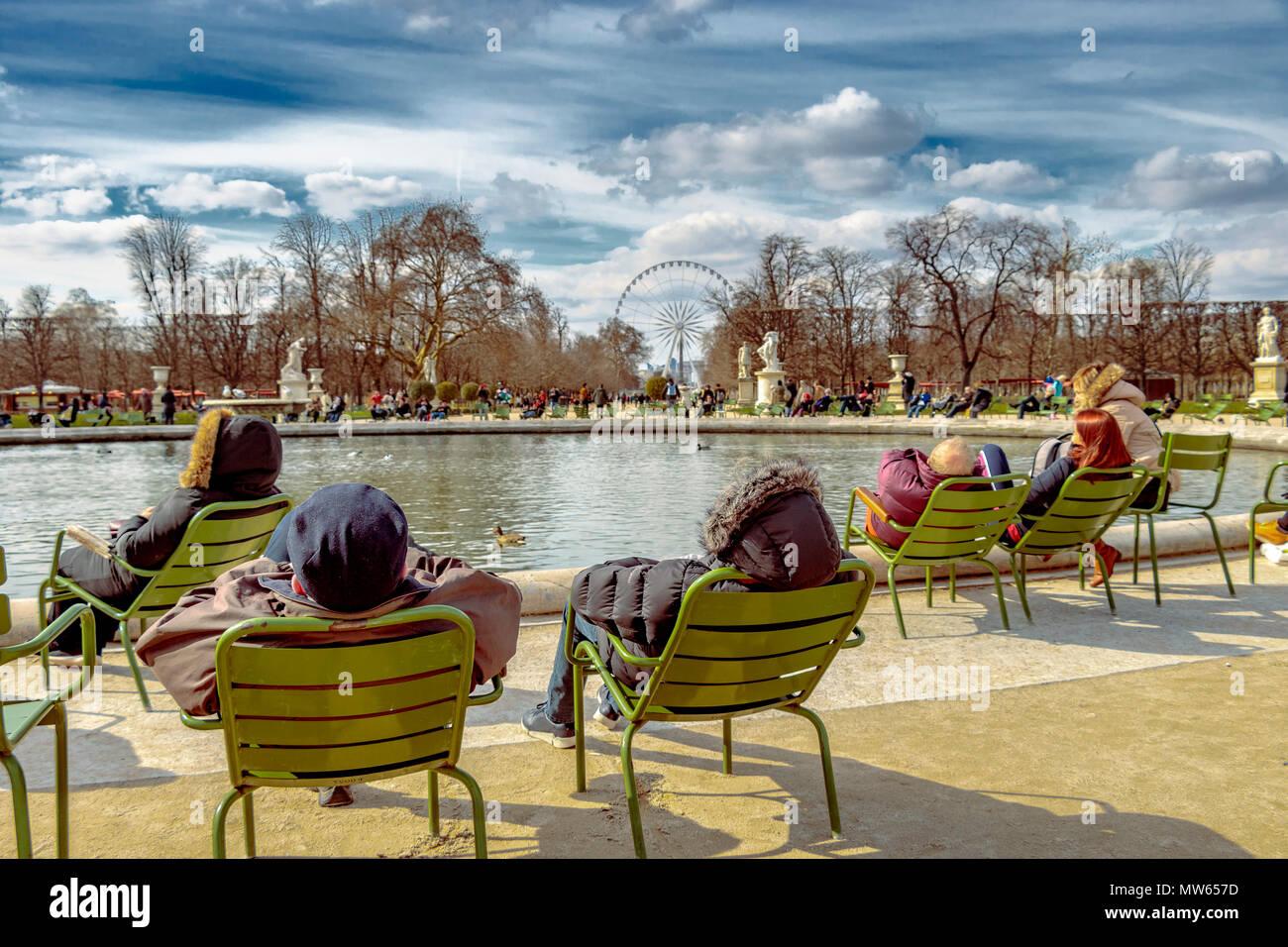 Des gens assis dans des chaises de détente dans le soleil d'hiver autour du Grand Bassin rond dans le Jardin des Tuileries, Paris, France Photo Stock