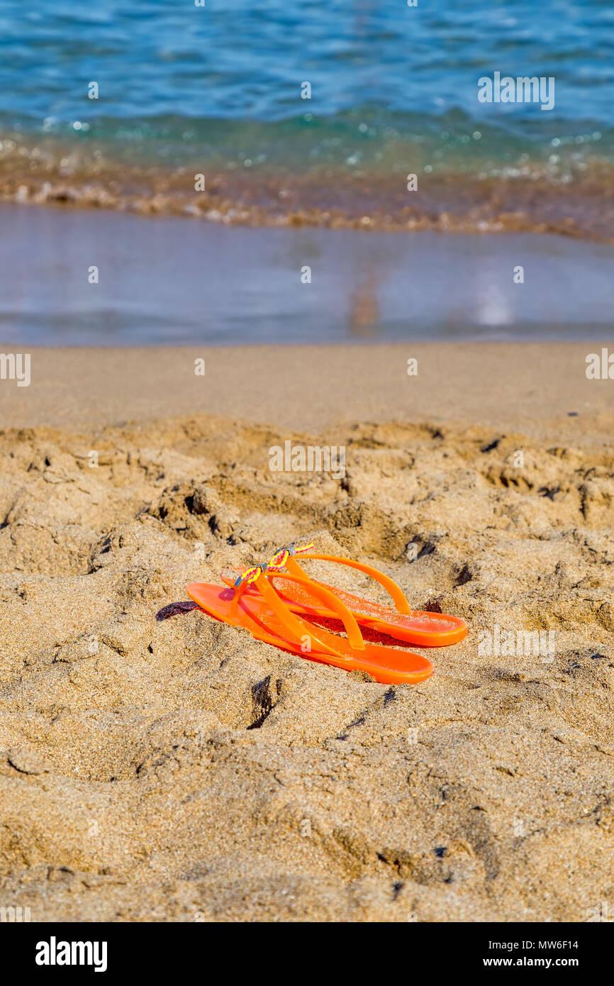 Paire de tongs orange sur la plage de sable fin. Banque D'Images
