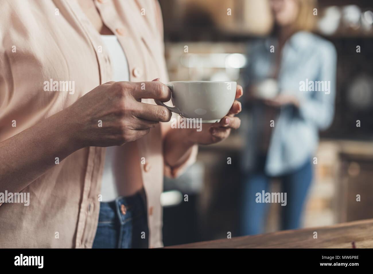 Image rognée, section centrale de personne holding Coffee cup, debout dans la cuisine Photo Stock