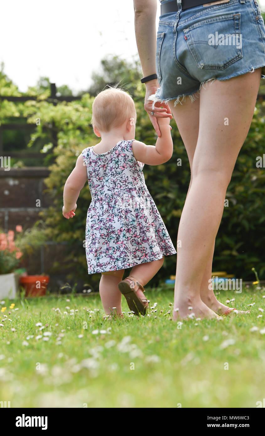 Belle Jeune fille bébé enfant à 18 mois avec des cheveux blonds courts walking in garden - modèle publié photographie prise par Simon Dack Photo Stock