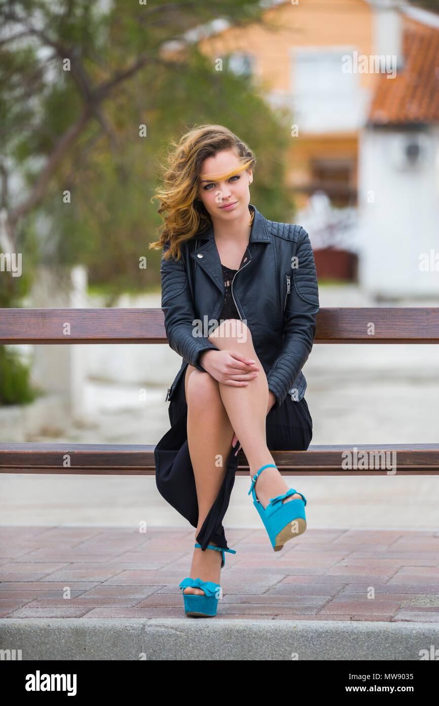 Une adolescente jambes talons assis sur un banc Photo Stock