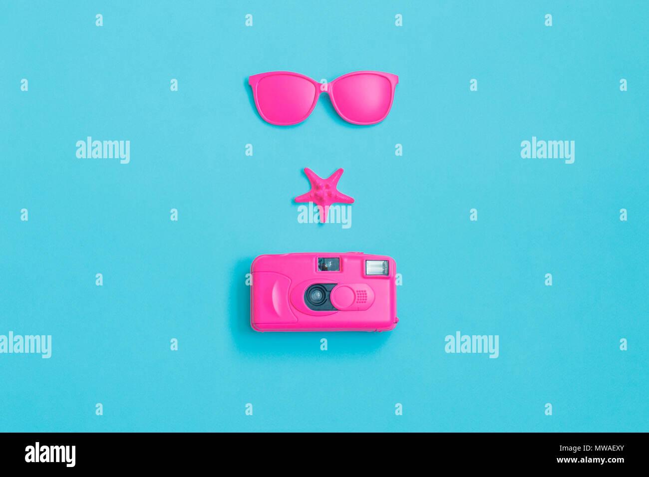 Lunettes roses, appareil photo et d'étoiles sur fond bleu. Concept minimal. Concept créatif. Été chaud. Lumineux Pop Art Sweet Fashion Style. Banque D'Images