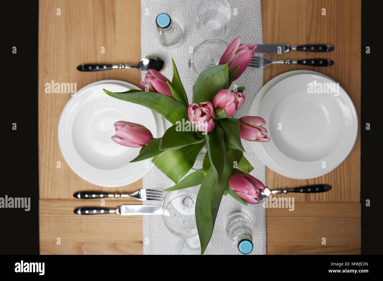 De la vaisselle avec des assiettes sur la table avec des fleurs dans un vase Banque D'Images