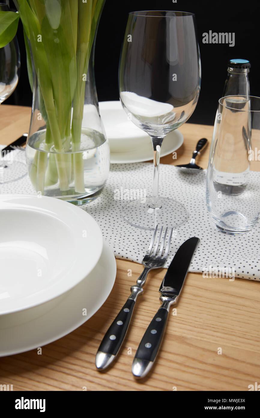 De la vaisselle avec des verres sur la table à côté de bouquet dans un vase Banque D'Images