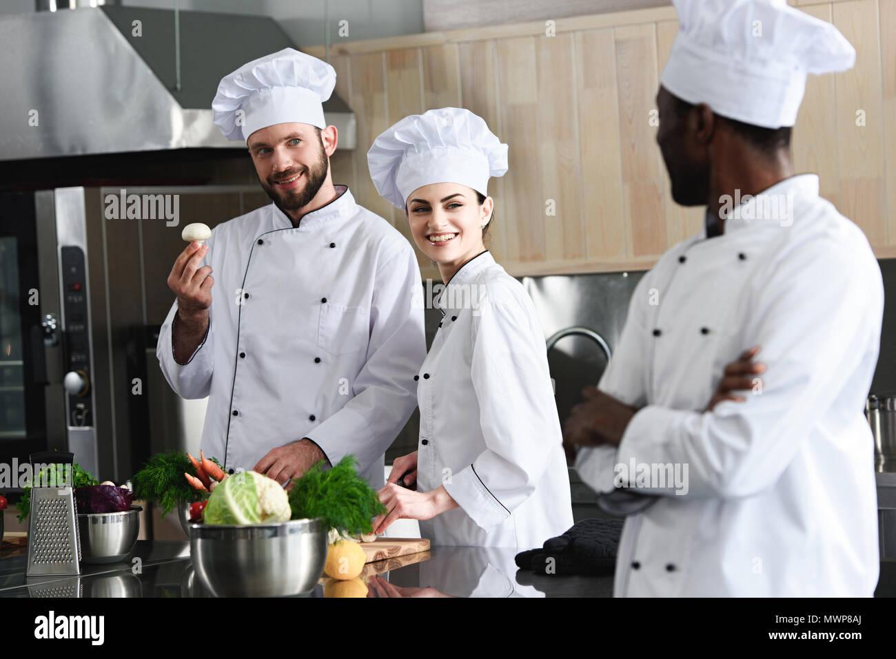Équipe de cuisiniers multiraciale choisissant sur ingrédients de cuisine cuisine moderne Photo Stock