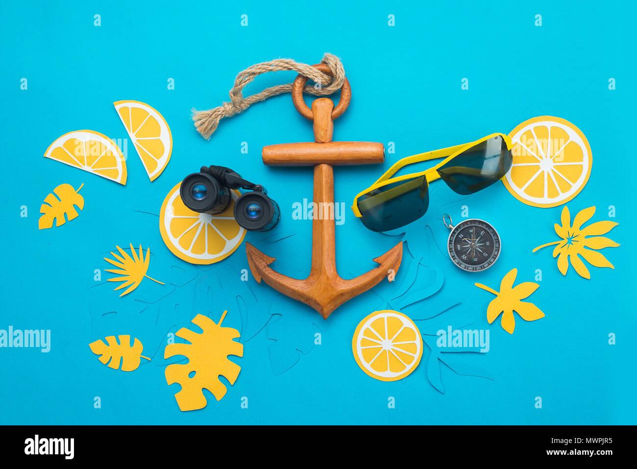Arrière-plan de voyage en mer avec des lunettes de soleil, jumelles, boussole, d'ancrage et de feuilles tropicales lumineuses sur un fond bleu. Vacances d'été avec concept copy space Photo Stock