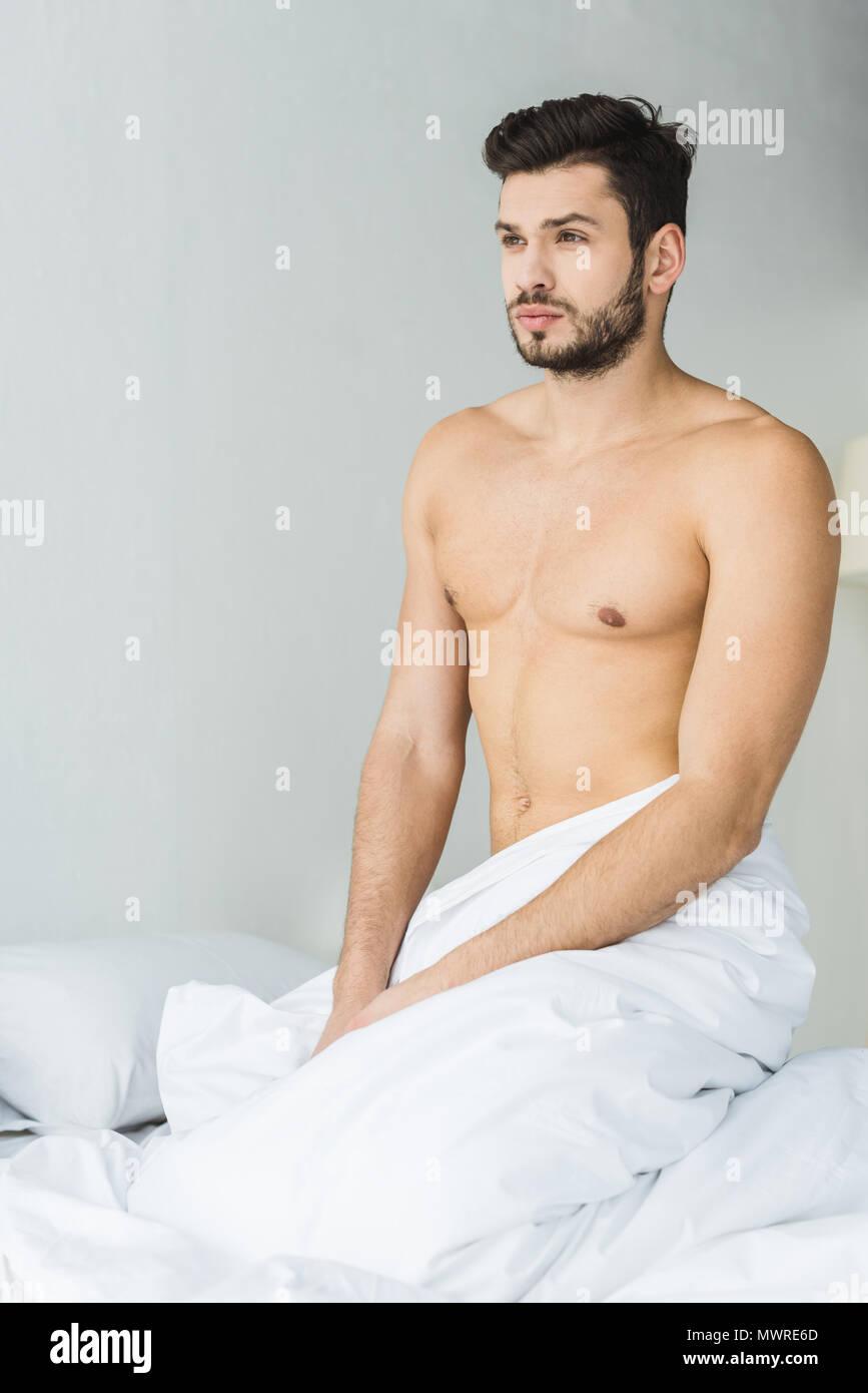 Homme Barbu Nu bel homme torse nu barbu assis sur un lit blanc banque d'images