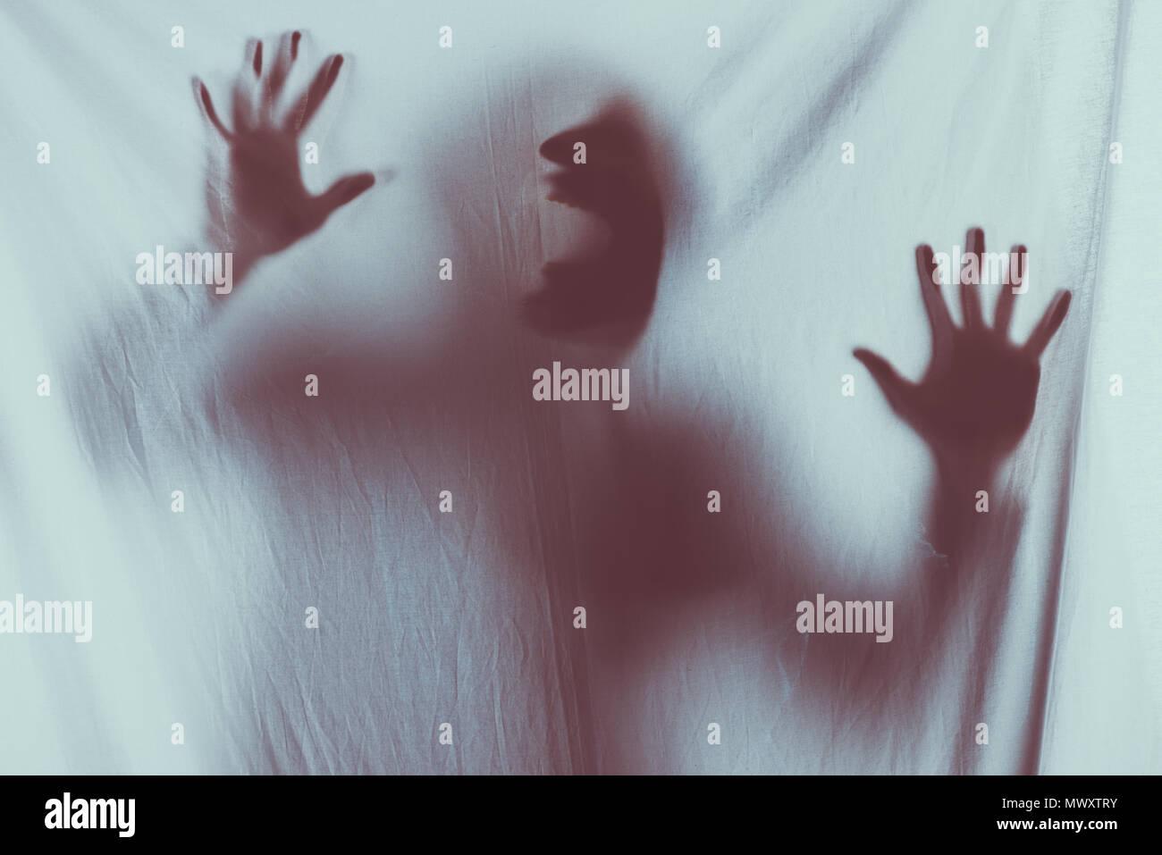 Silhouette floue effrayant de méconnaissable personne crier derrière voile Photo Stock