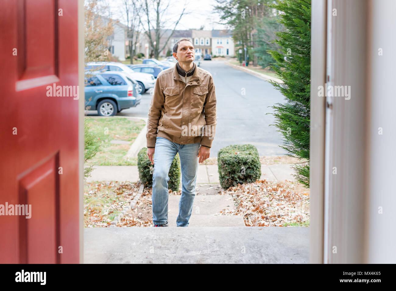 Jeune homme debout sur le porche étapes frontyard in front of house accueil acheteur à la recherche d'acheter un bien immobilier en client client résident townhouse Banque D'Images