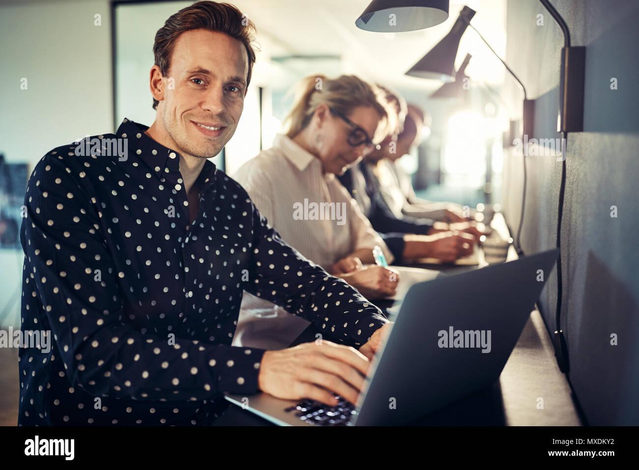 Smiling young designer travaillant sur un ordinateur portable tout en étant assis dans une rangée avec des collègues à une table dans un bureau moderne Photo Stock