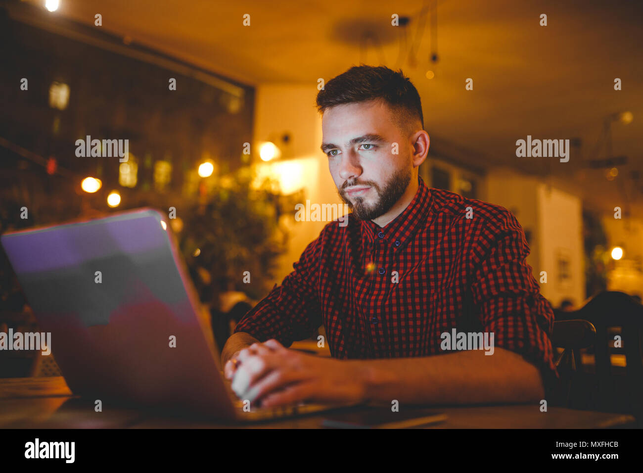 Un beau jeune homme de race blanche avec barbe et sourire à pleines dents dans une chemise à carreaux rouge fonctionne derrière un ordinateur portable gris assis à une table en bois. Les mains sur le clavier. Dans la soirée au café Photo Stock