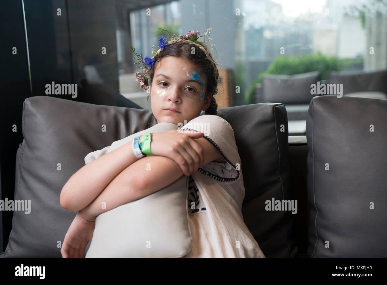 Un pré-adolescent pensif avec la peinture pour le visage et une couronne de fleurs à Brooklyn, New York. Photo Stock