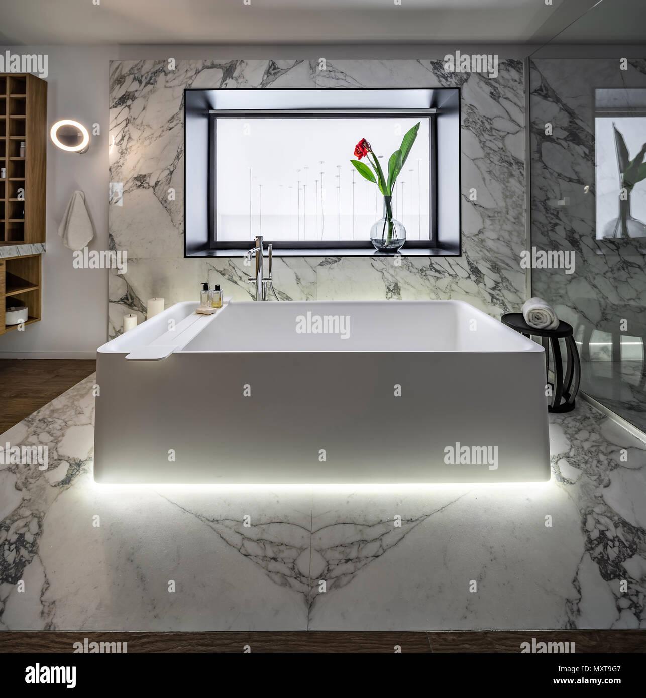 Belle salle de bains moderne avec des murs blancs et un sol carrelé ...
