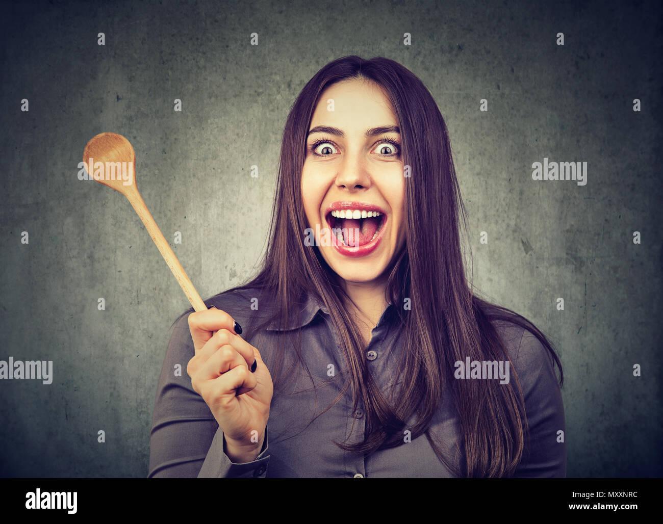 Jeune femme à la caméra à fou avec expression drole de maladie de la femme au foyer et holding cuillère en bois Photo Stock