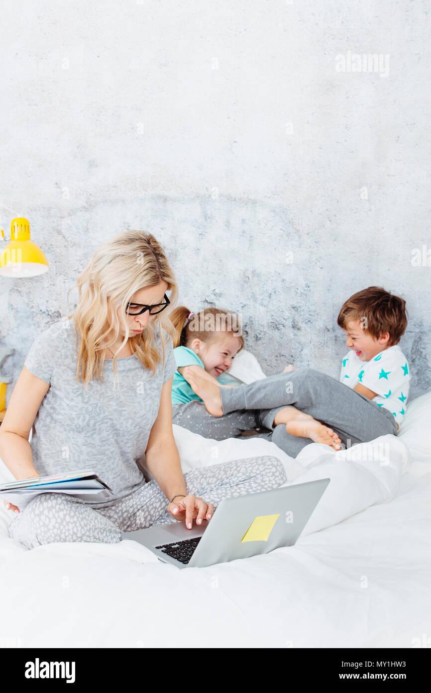 Maman d'affaires au travail tandis que ses enfants jouent au lit Photo Stock