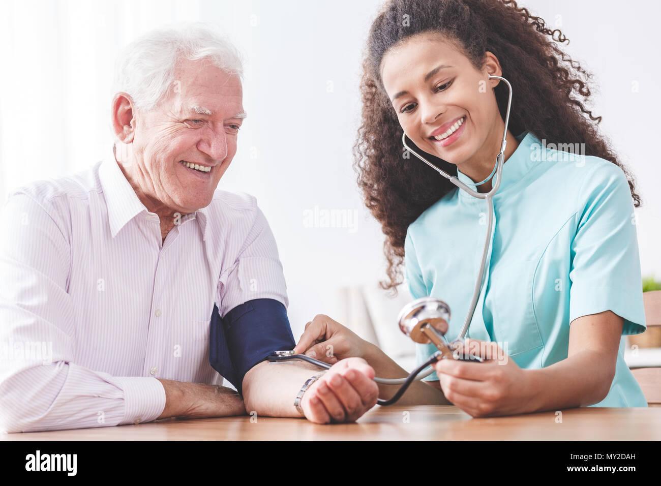 Jeune infirmière la mesure de la pression artérielle d'un vieil homme heureux à l'hôpital. Le concept de rétablissement réussi Banque D'Images