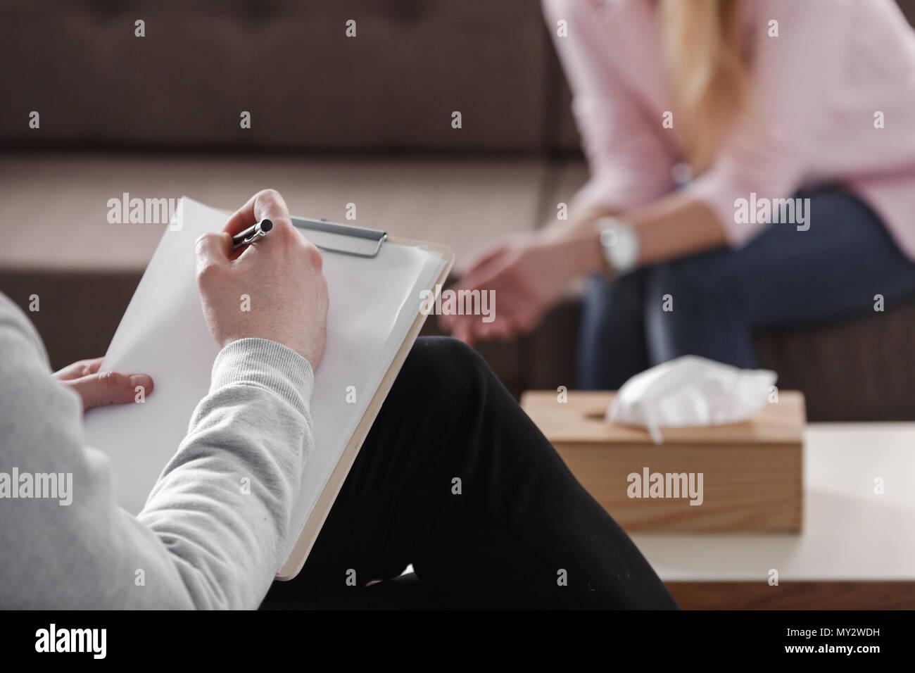 Close-up du thérapeute part la rédaction de notes au cours d'une séance de counseling avec une seule femme assise sur un canapé dans l'arrière-plan flou. Banque D'Images