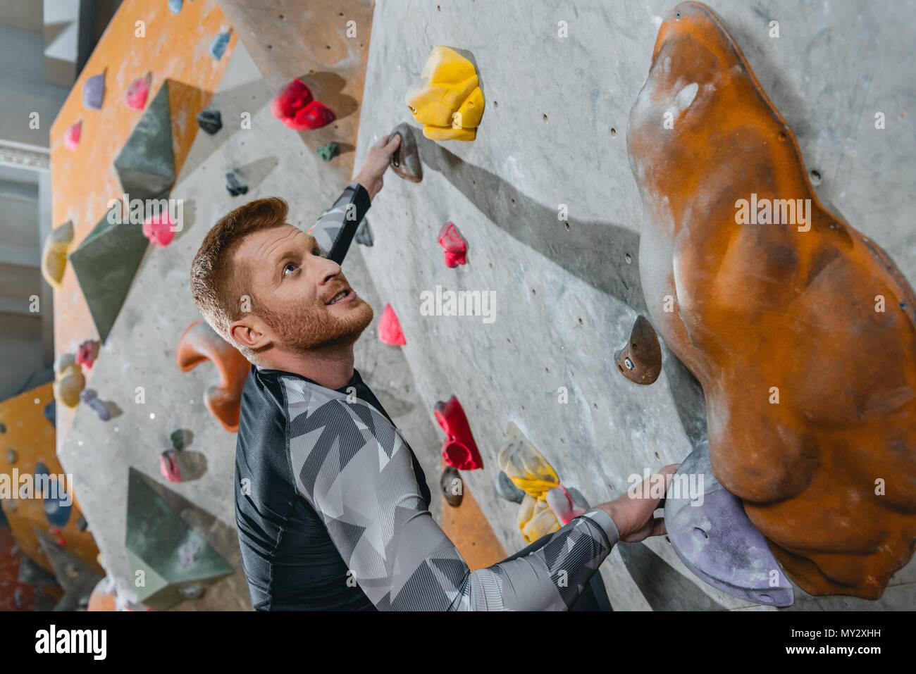 Coup de demi-longueur de jeune homme dans une tenue sportive escalade un mur avec prises at gym Photo Stock