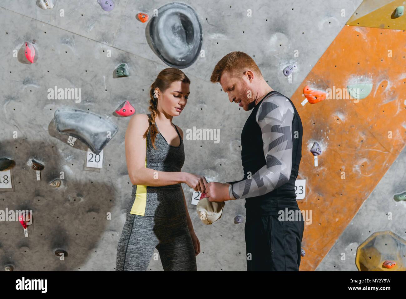 La moitié de la longueur de l'homme et la femme dans une tenue sportive d'appliquer du talc sur les mains d'un sac Photo Stock