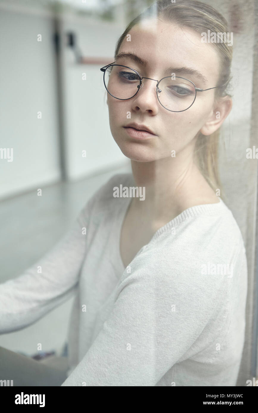 Jeune femme à la recherche d'une fenêtre, portrait Photo Stock