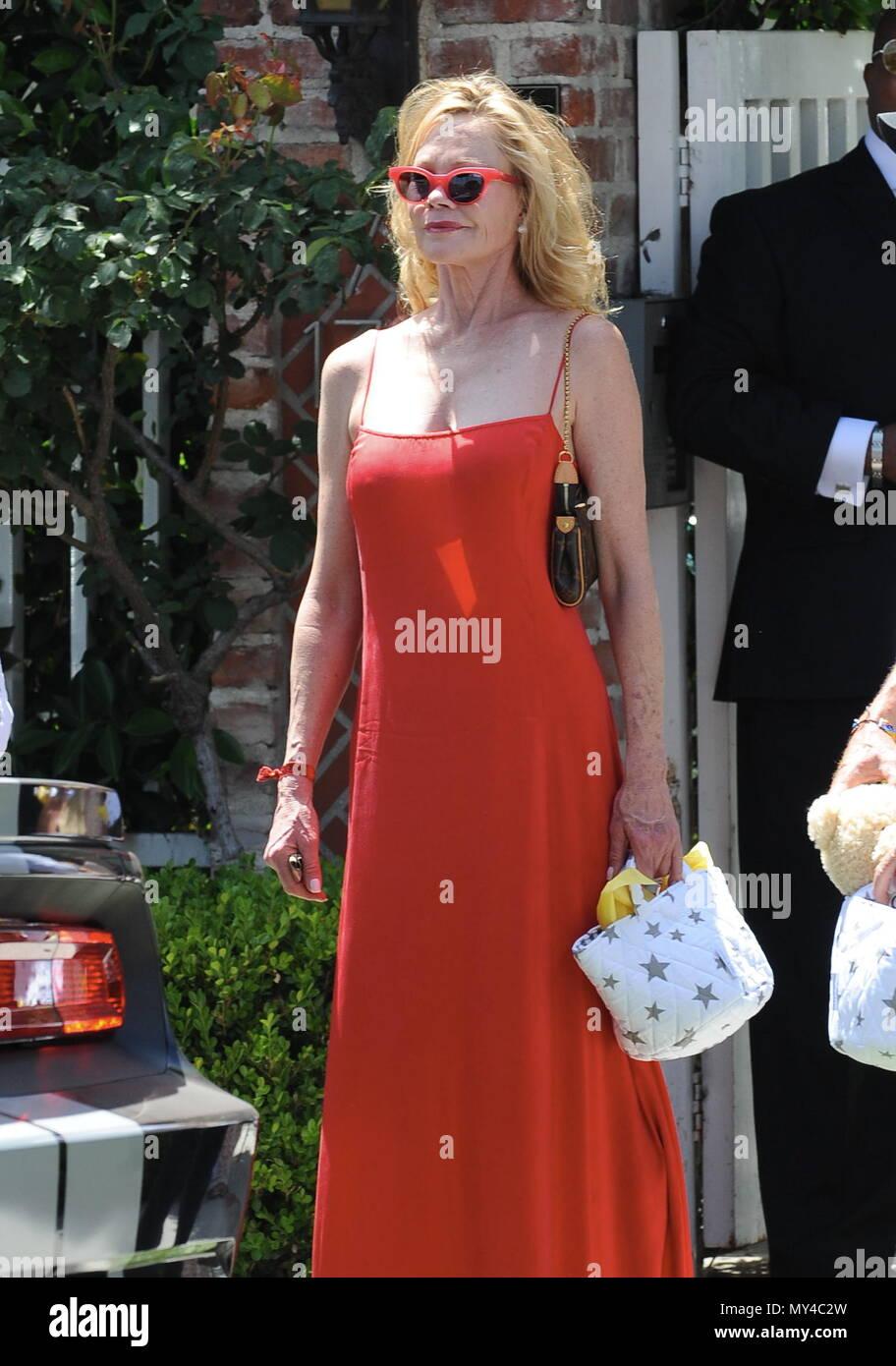 L actrice Melanie Griffith assiste à la douche de bébé Eva Longoria dans  une robe rouge transparente et une forme de coeur lunettes de soleil. 290d9709598d