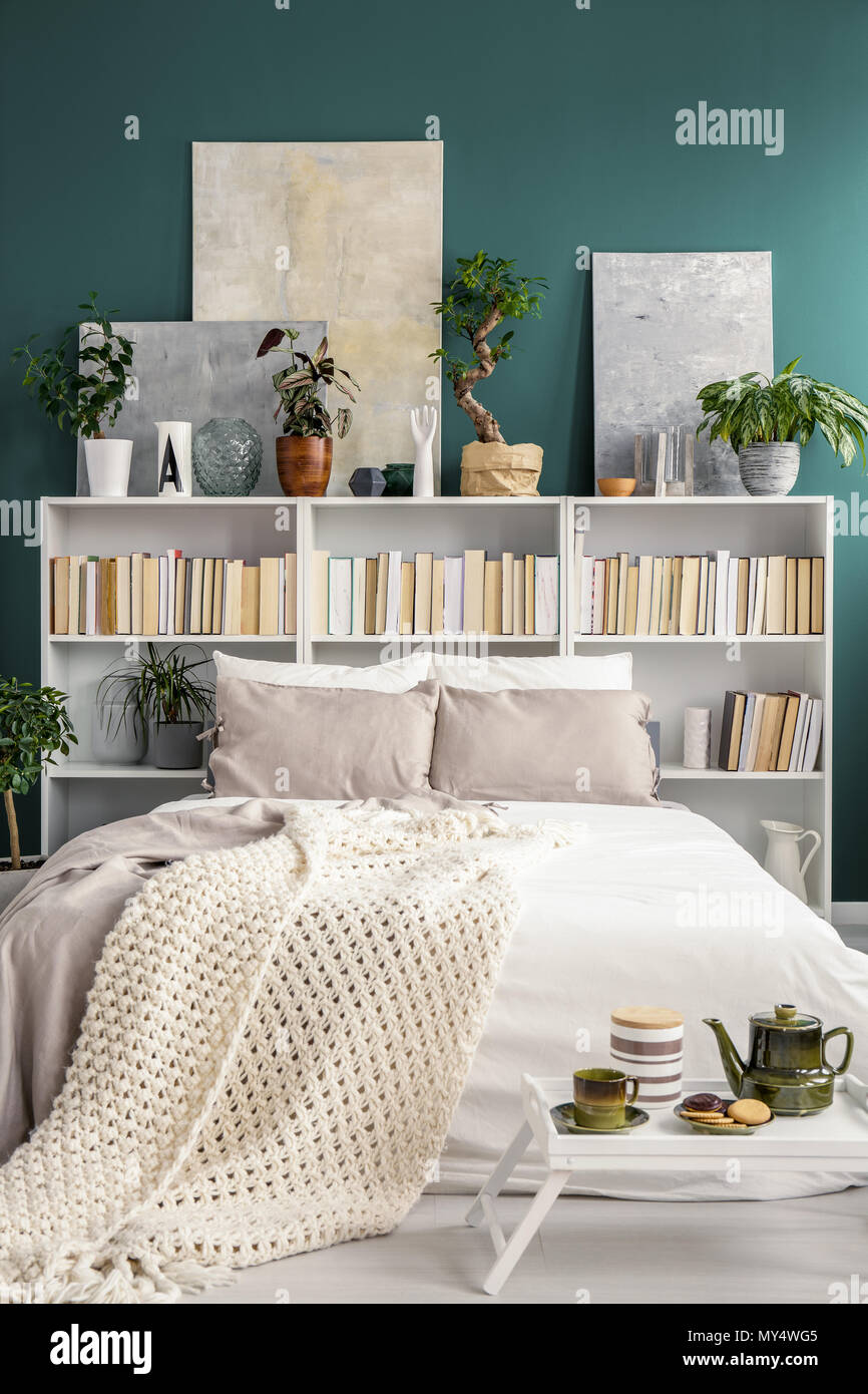 Étagère blanche derrière un double lit avec couverture et oreillers ...