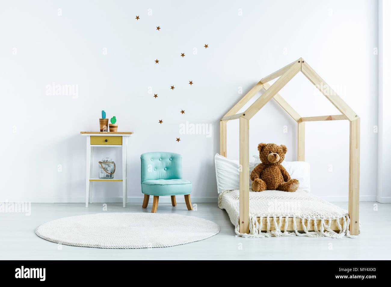 Ours sur lit en bois à côté du fauteuil bleu blanc dans la chambre de l'enfant intérieur. Photo réelle Banque D'Images