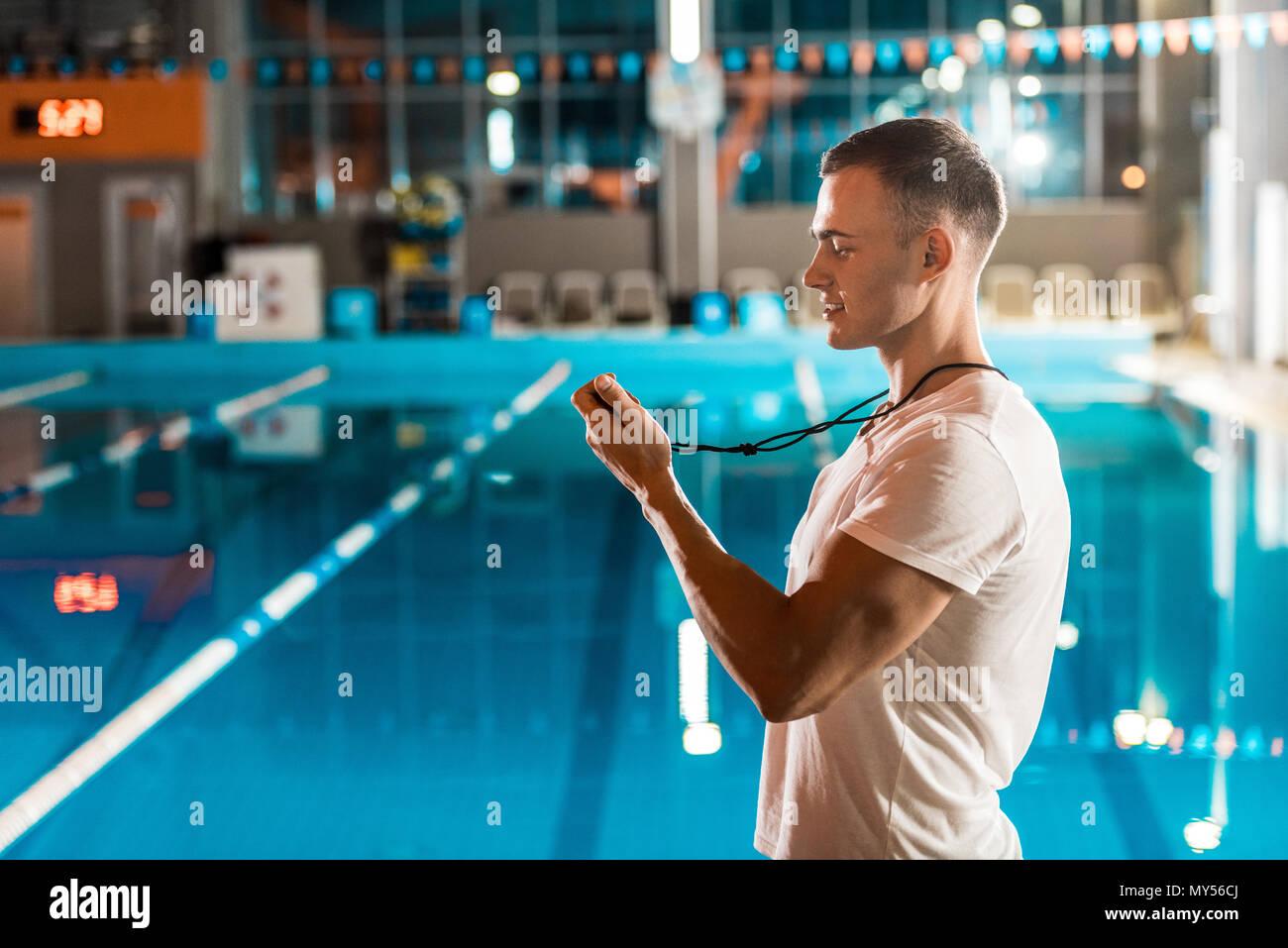 Beau entraîneur de natation avec chronomètre à la concurrence piscine Photo Stock
