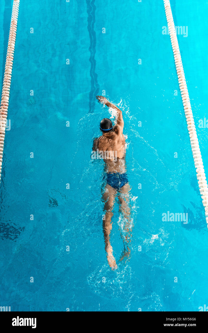 Athletic swimmer in cap and goggles swimming in pool Photo Stock